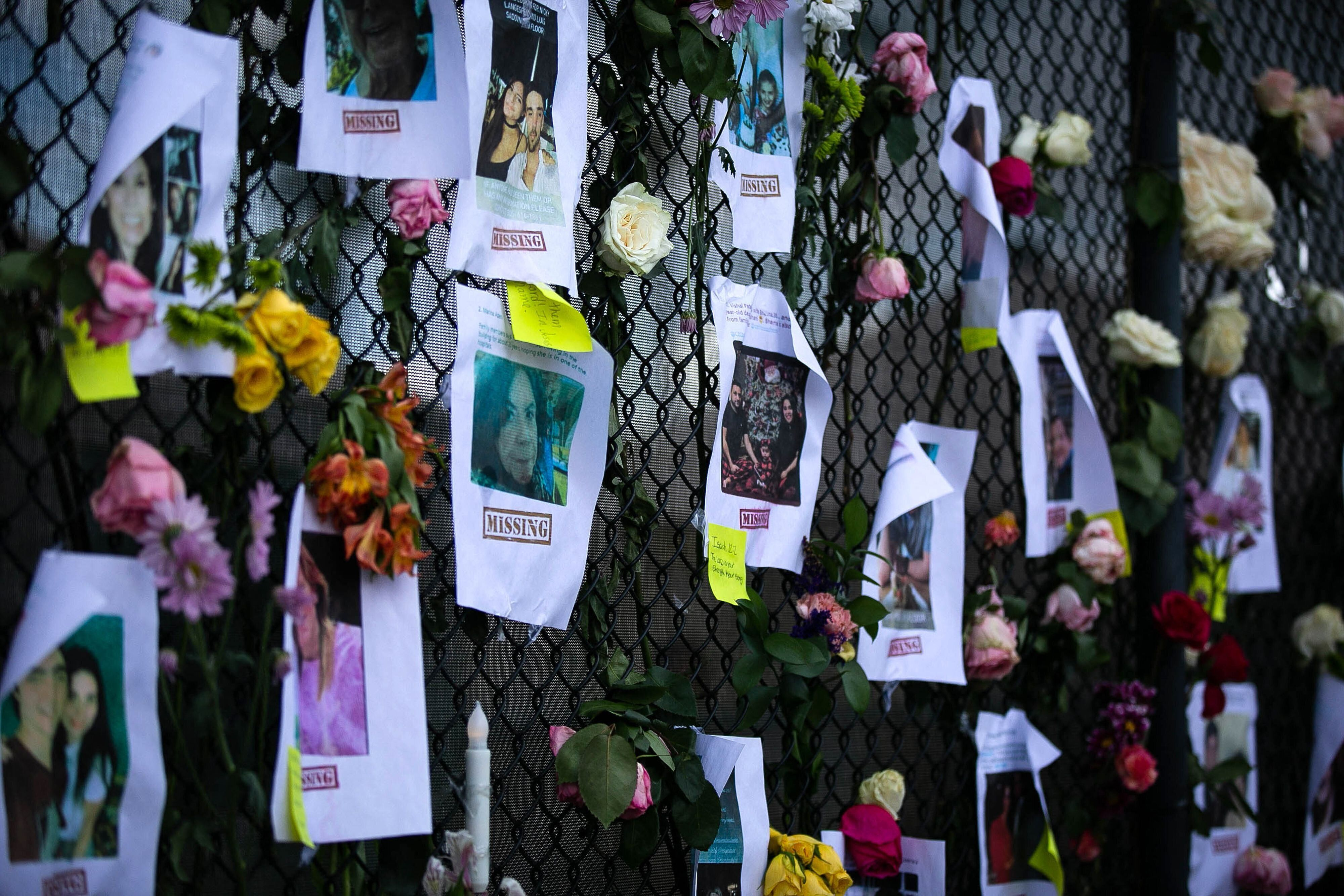Photos of missing residents are posted at a makeshift memorial at the site of the collapsed building in Surfside.