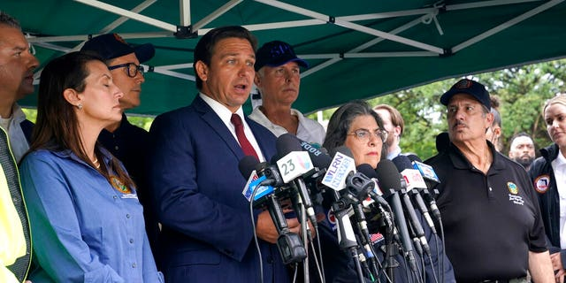 Florida Gov. Ron DeSantis, second from left, speaks during a news conference near the scene where a wing of a 12-story beachfront condo building collapsed, Thursday, June 24, 2021, in the Surfside area of Miami. At left is Lt. Gov. Jeanette Nunez, (AP Photo/Lynne Sladky)