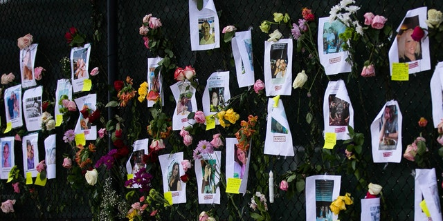 """Photos of missing residents are posted at a makeshift memorial at the site of a collapsed building in Surfside, Florida, north of Miami Beach,on June 26, 2021. - An engineer warned of """"major structural damage"""" at a Florida apartment building three years before it partially collapsed, a report said June 26, as rescuers raced to find 159 people still unaccounted for in the mountain of debris. Four people have been confirmed dead after the 12-story oceanfront building in Surfside pancaked as residents slept inside in the early hours of June 24. (Photo by Andrea SARCOS / AFP) (Photo by ANDREA SARCOS/AFP via Getty Images)"""