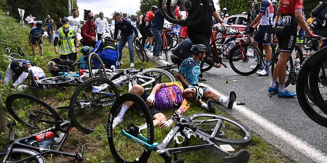Italy's Kristian Sbaragli, left, and France's Bryan Coquard, right, lie on the ground after crashing during the first stage of the Tour de France cycling race Saturday, June 26, 2021. (Anne-Christine Poujoulat, Pool Photo via AP)