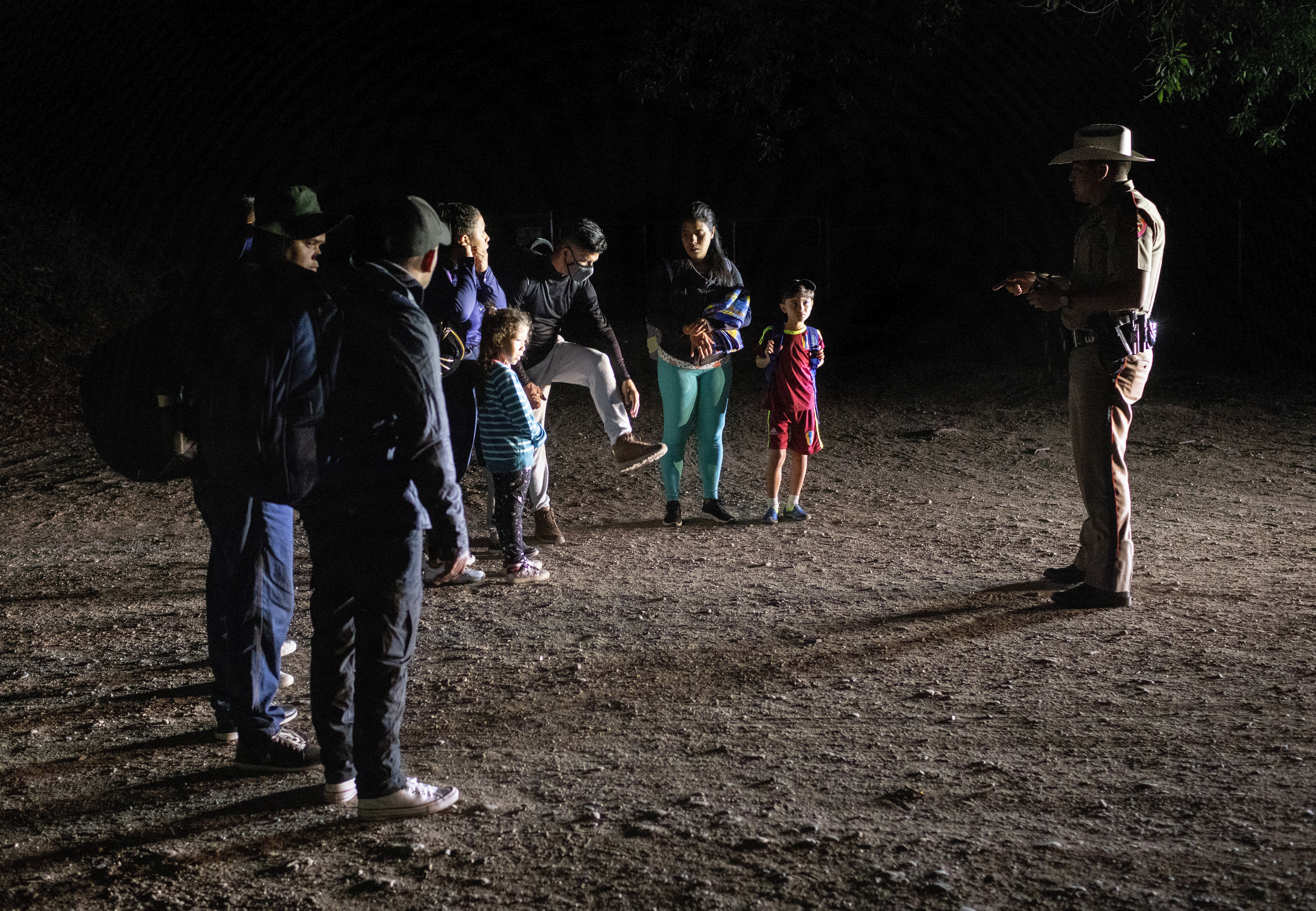 A Texas state trooper advises Venezuelan immigrants to remove their shoelaces before they are taken into custody by U.S. Bord
