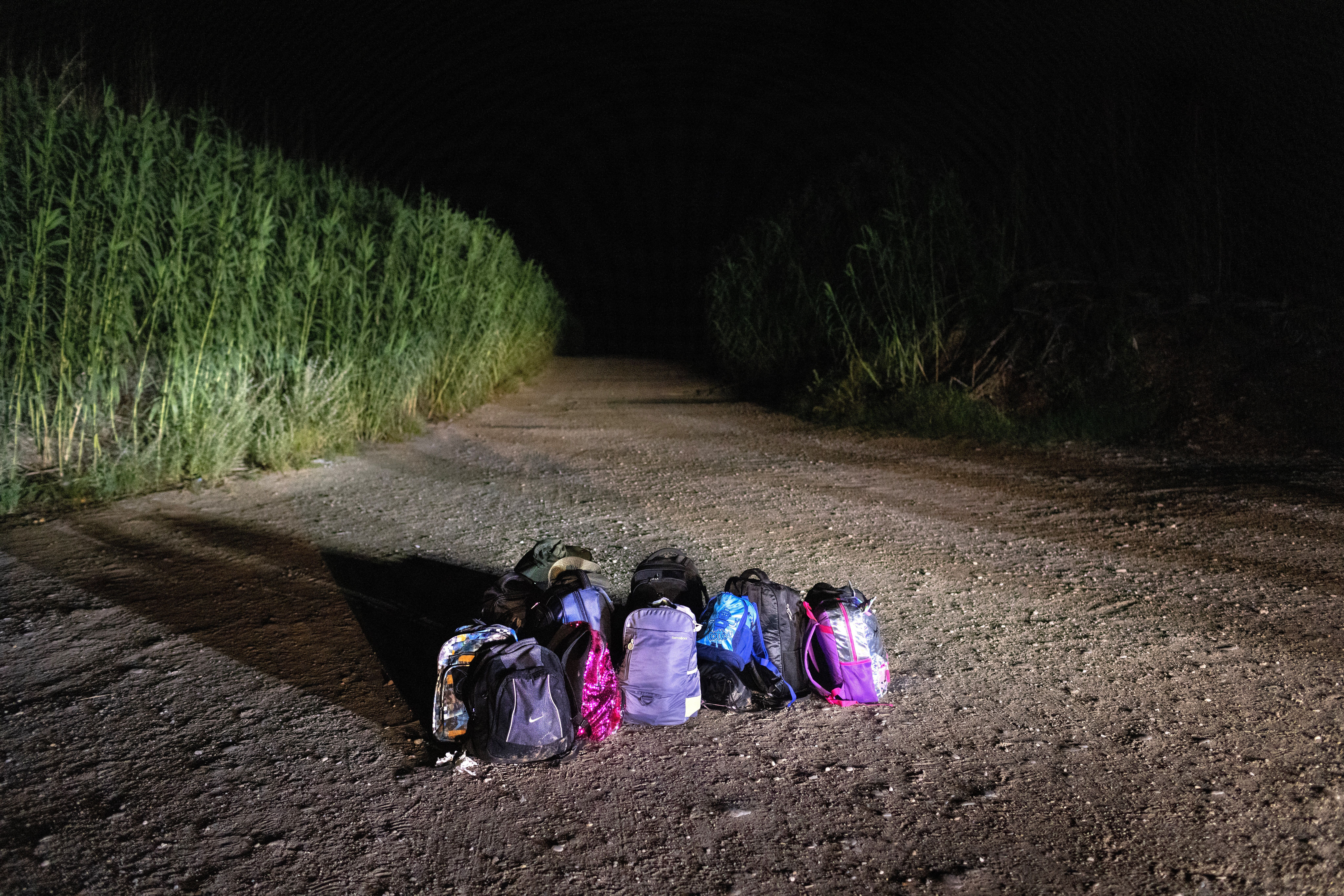 Backpacks lie in the road to be collected by U.S. Border Patrol agents after a group of Venezuelan immigrants was taken into