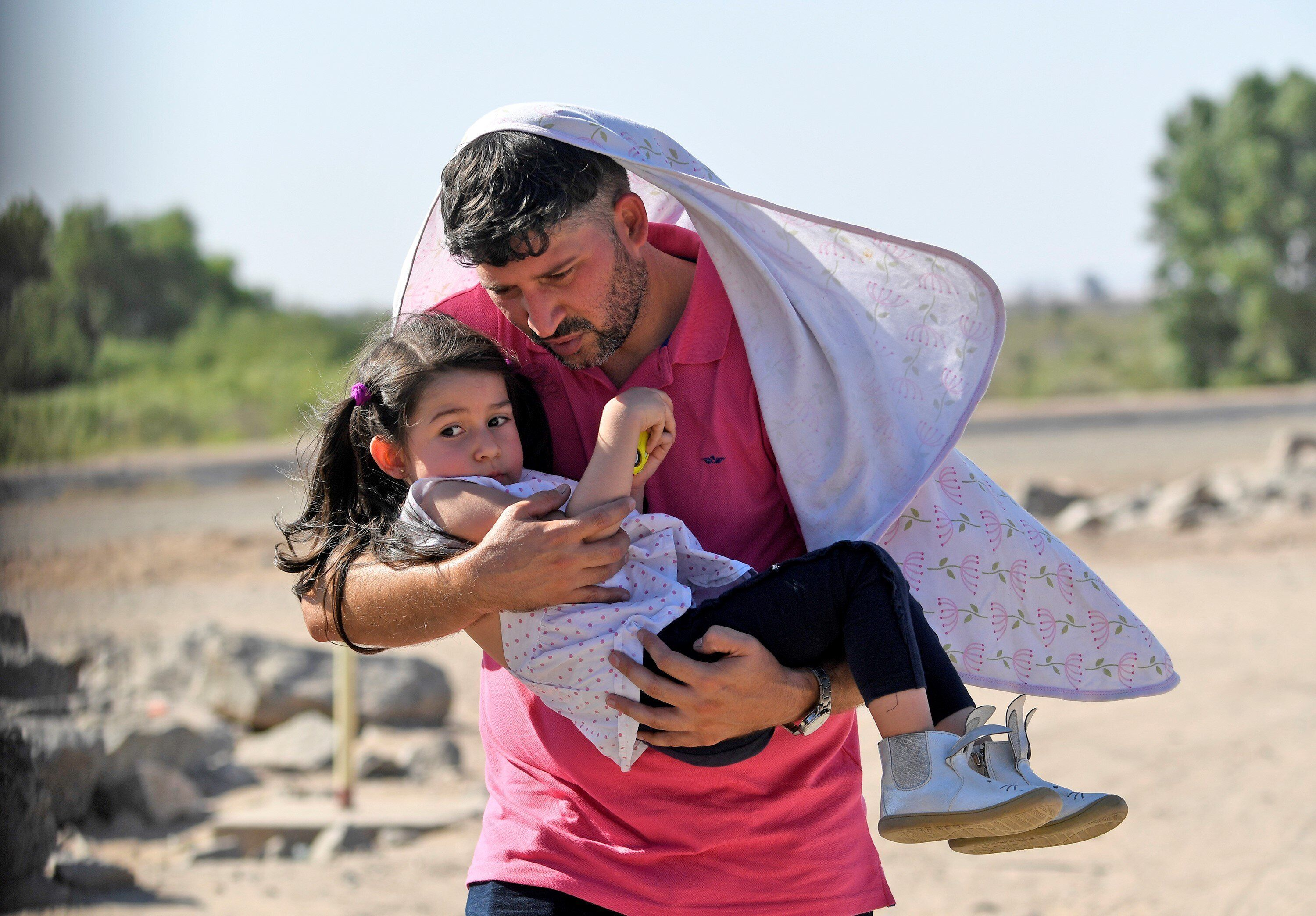 Luis Sarcos from Venezuela holds his daughter Luna as they attempt to cross into the U.S. from Mexico on June 4 in San Luis,