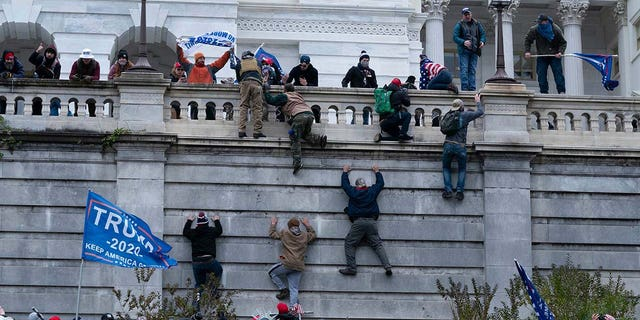 Supporters of former President Donald Trump climb the west wall of the the U.S. Capitol on Wednesday, Jan. 6, 2021, in Washington. (AP Photo/Jose Luis Magana)