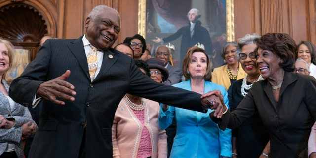 House Majority Whip James Clyburn, D-S.C., center left, reaches over to Rep. Maxine Waters, D-Calif., joined by Speaker of the House Nancy Pelosi, D-Calif., center, and members of the Congressional Black Caucus. (AP Photo/J. Scott Applewhite)