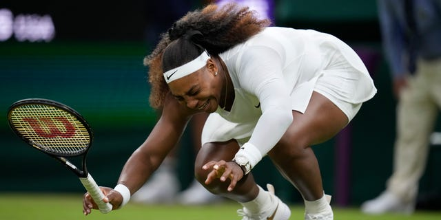 Serena Williams of the U.S. falls to the ground during the women's singles first- round match against Aliaksandra Sasnovich of Belarus on day two of the Wimbledon Tennis Championships in London, Tuesday June 29, 2021. (AP Photo/Kirsty Wigglesworth)