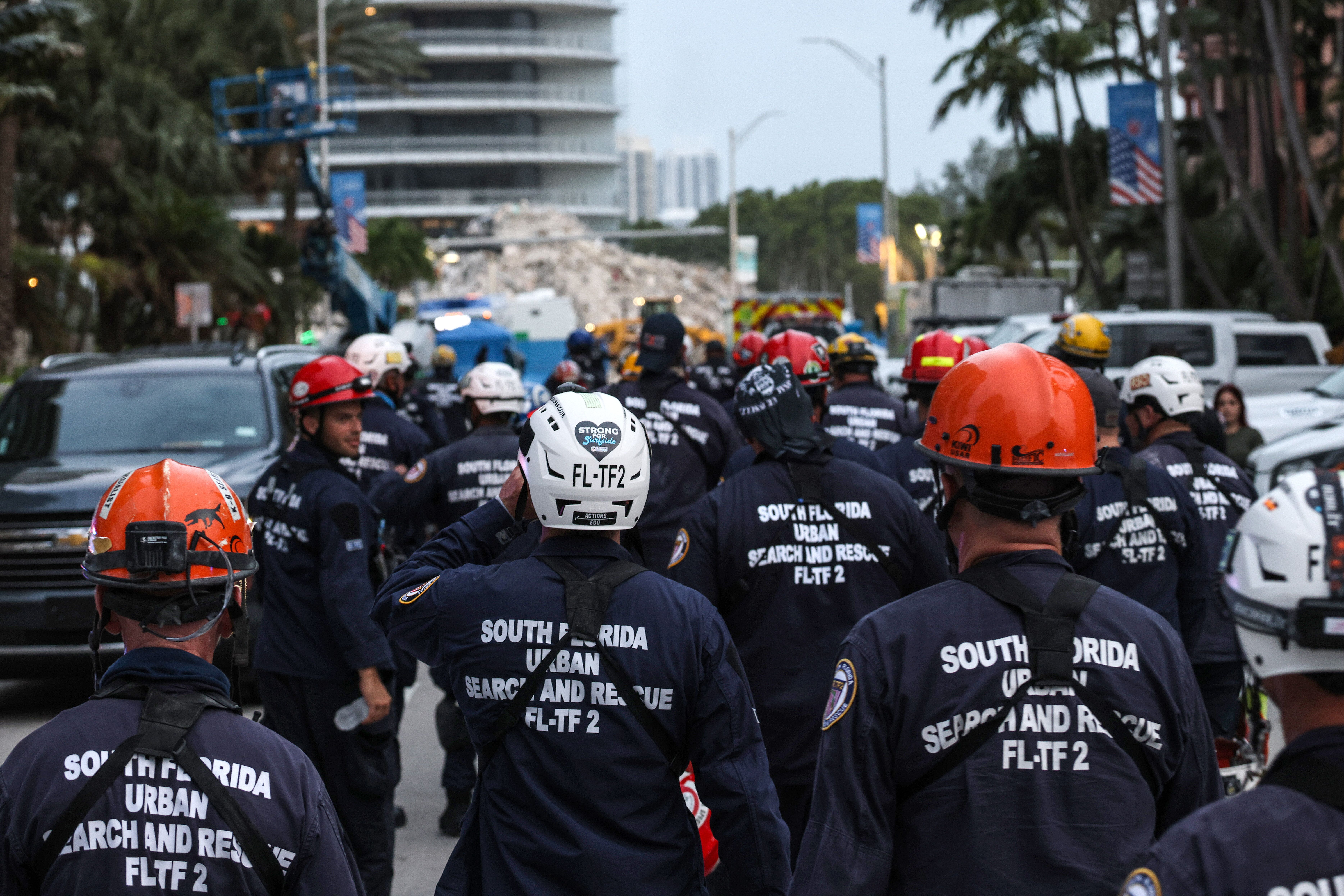 Search and rescue personnel walk back to work on the recovery operation at the collapsed 12-story Champlain Towers South cond
