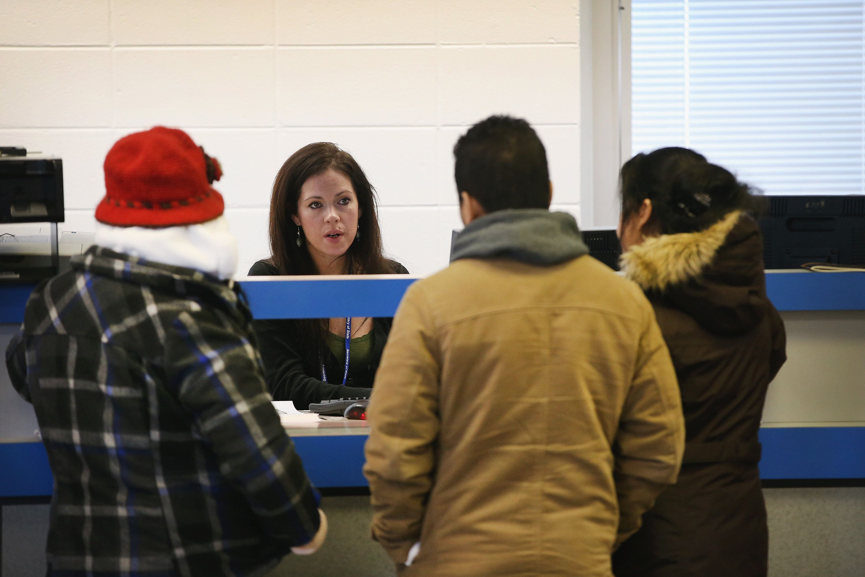 Residents apply for or renew their driver's licenses at a driver services facility on Dec. 10, 2013, in Chicago. Illinois' Te