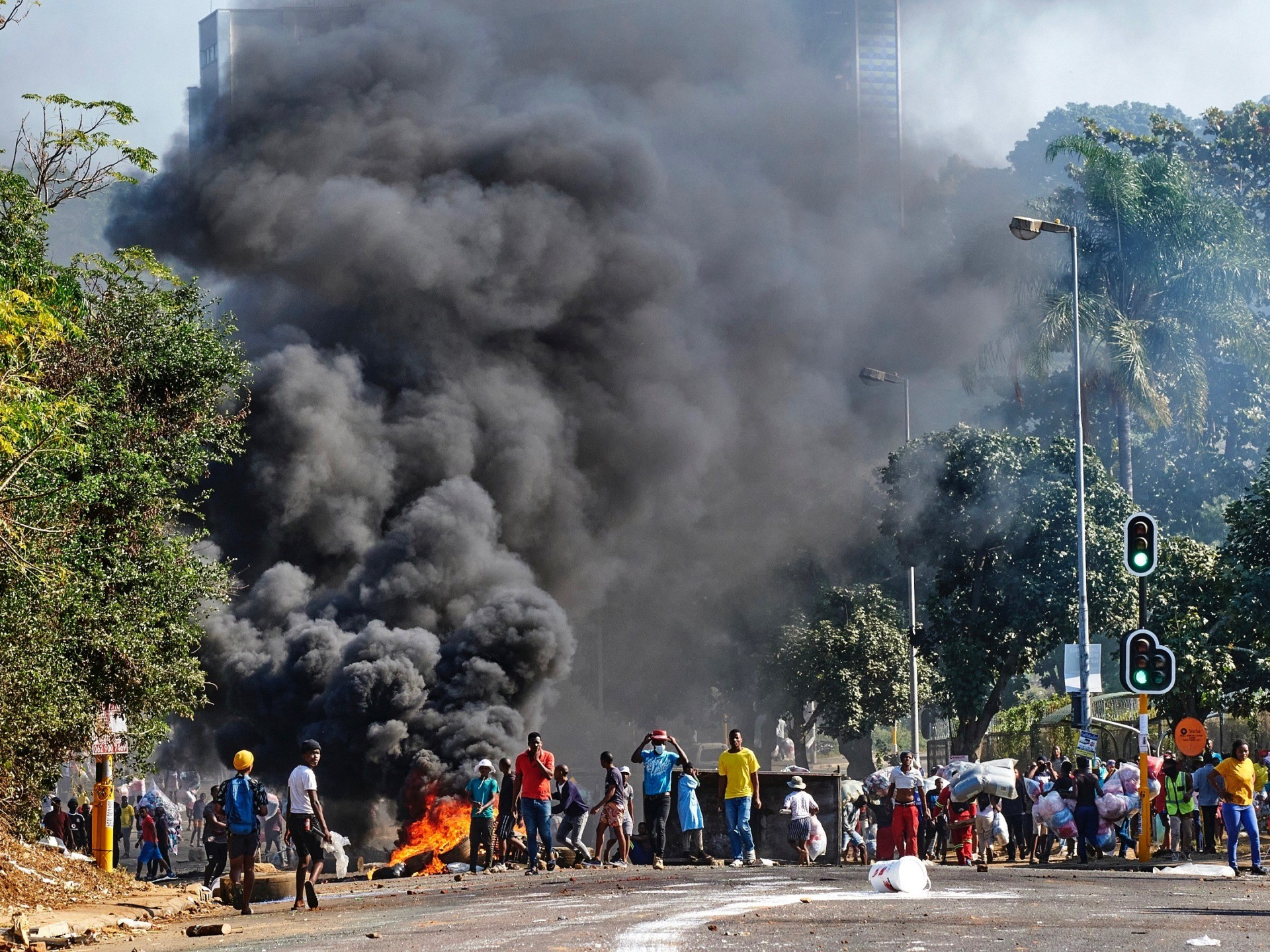 Looters outside a shopping centre alongside a burning barricade in Durban, South Africa, Monday July 12, 2021. Police say six people are dead and more than 200 have been arrested amid escalating violence during rioting that broke out following the imprisonment of South Africa's former President Jacob Zuma. (AP Photo/Andre Swart)