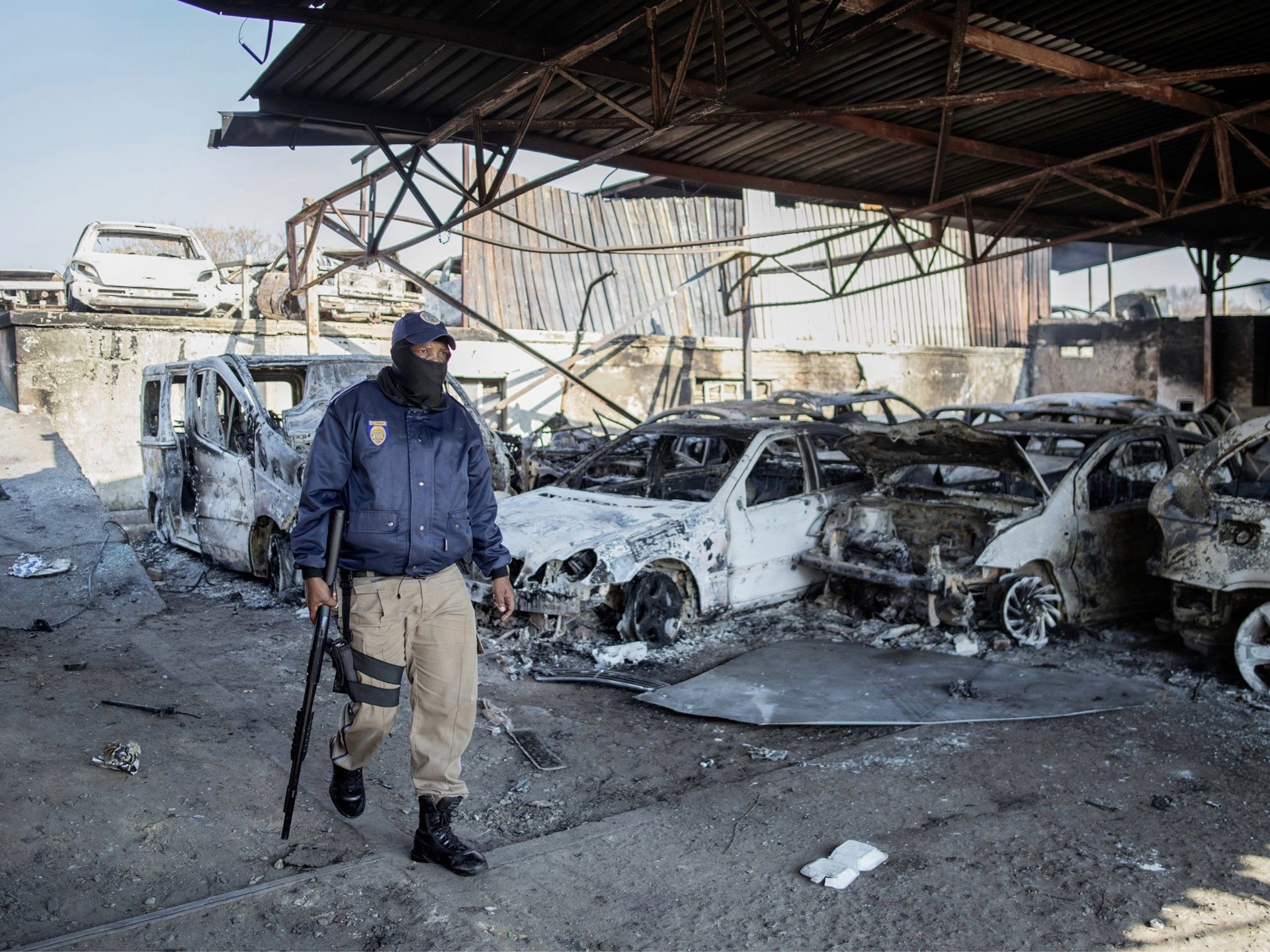 A Johannesburg Metro Police Department (JMPD) officer walks past the wreckage of burnt cars at a car showroom in Jeppestown district, Johannesburg, on July 11, 2021. - Several shops are damaged and cars burnt in Jeppestown, Johannesburg, following a night of violence. Police are on the scene trying to control further protests. It is unclear if this is linked to sporadic protests following the incarceration of former president Jacob Zuma. (Photo by LUCA SOLA / AFP) (Photo by LUCA SOLA/AFP via Getty Images)