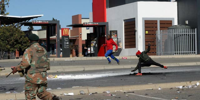 A soldier apprehends a looters at a shopping centre in Soweto near Johannesburg, Tuesday July 13, 2021 as ongoing looting and violence continues.