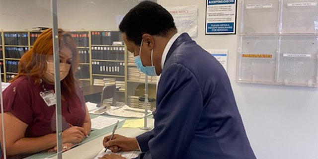 Conservative radio host and attorney Larry Elder signs paperwork to get on the Sept. 14 recall ballot at the Los Angeles County Registrar's Office Tuesday.
