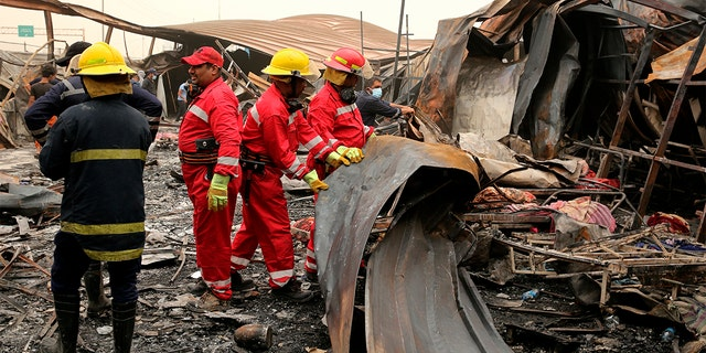 Rescuers look for bodies after a catastrophic blaze erupted Monday at a coronavirus hospital ward in the al-Hussein Teaching Hospital, in Nasiriyah, Iraq, Tuesday, July 13, 2021.