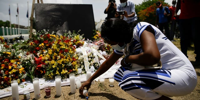 A woman lights a candle at a memorial outside the Presidential Palace in memory of slain President Jovenel Moise in Port-au-Prince, Haiti, Wednesday, July 14, 2021, a week after Moise was assassinated in his home. (AP Photo/Joseph Odelyn)
