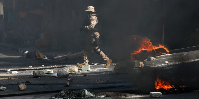 Police work to clear a road blocked by rocks and tires set fire by protesters upset with growing violence in the Lalue neighborhood of Port-au-Prince, Haiti, Wednesday, July 14, 2021. Haitian President Jovenel Moise was assassinated on July 7. (AP Photo/Fernando Llano)