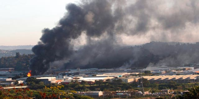A building burns near Durban South Africa, Thursday, July 15, 2021, as unrest continues in the KwaZulu Natal province.