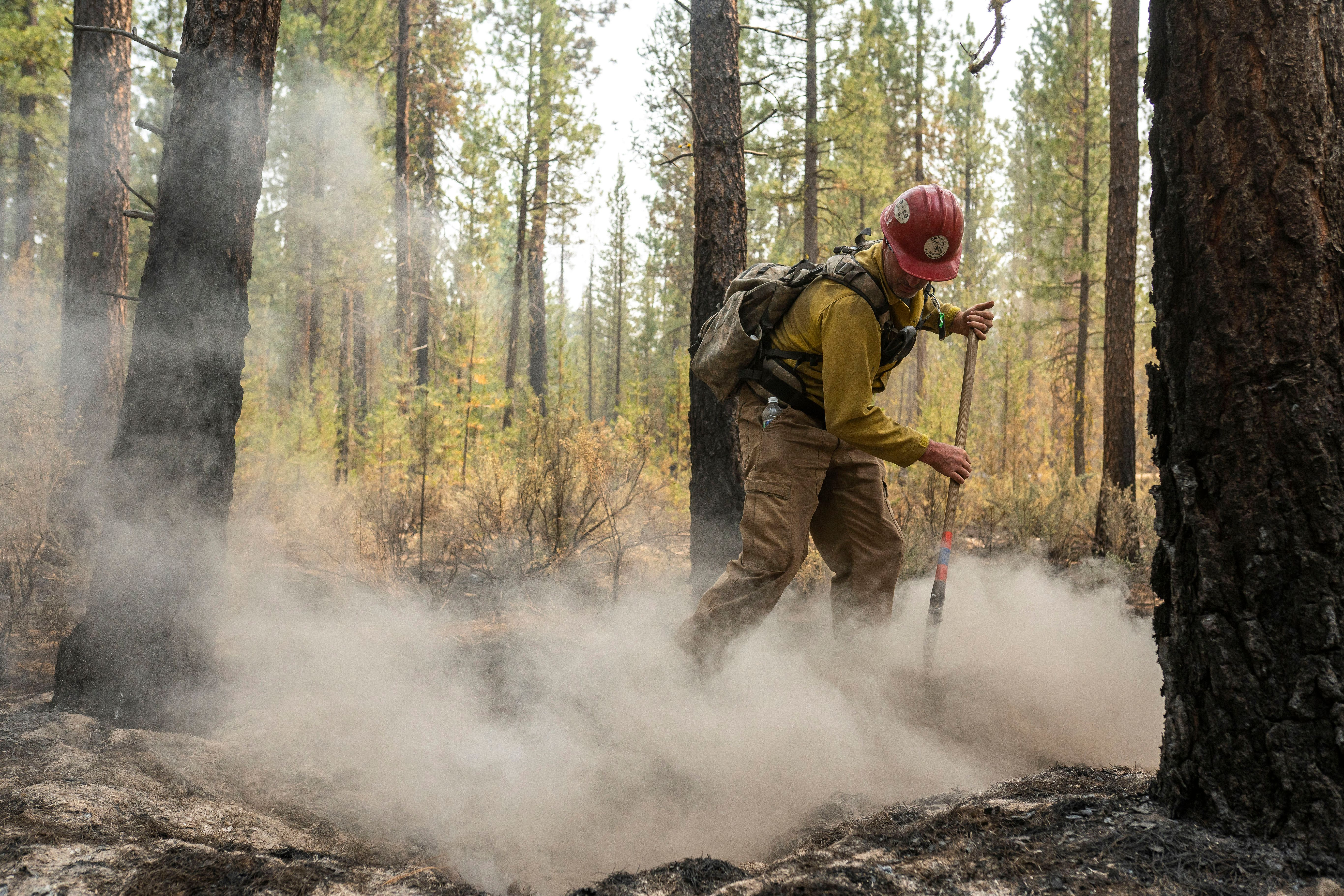 Firefighter Garrett Suza, with the Chiloquin Forest Service, mops up a hot spot on the North East side of the Bootleg Fire.