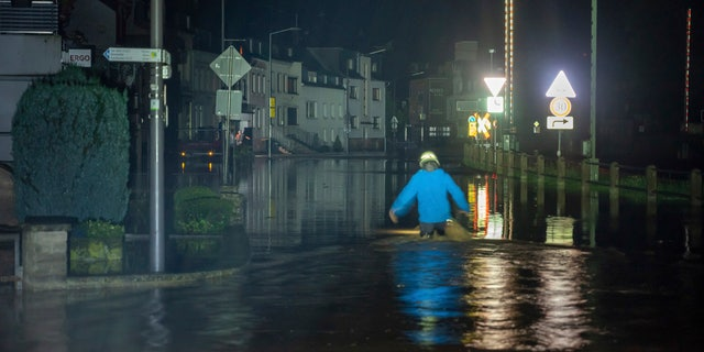 A firefighter wades through a street in Kordel, Germany, which was flooded by the Kyll River, early Thursday, July 15, 2021. Continuous rainfall has flooded numerous villages and cellars in Rhineland-Palatinate, southwestern Germany. (Harald Tittel/dpa ia AP)