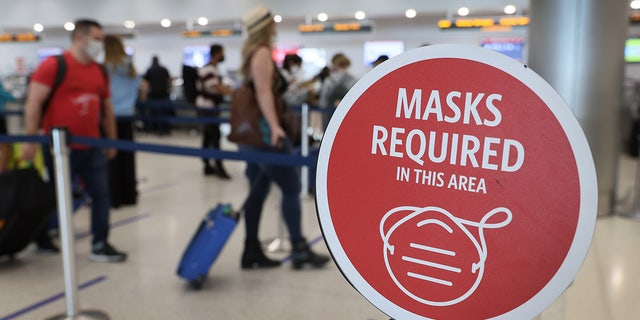 """A sign reading """"Masks required in this area"""" is seen as travelers prepare to check in for their Delta Airlines flight at the Miami International Airport on Feb. 1, 2021, in Miami, Fla. (Joe Raedle/Getty Images)"""