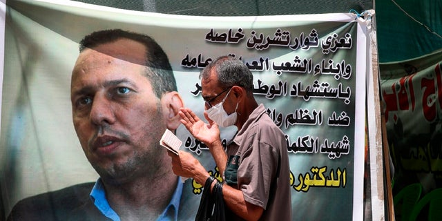In this July 12, 2020 file photo, a protester prays by a poster showing Hisham al-Hashimi an Iraqi analyst who was a leading expert on the Islamic State and other armed groups who was shot dead in Baghdad. (AP Photo/Khalid Mohammed)