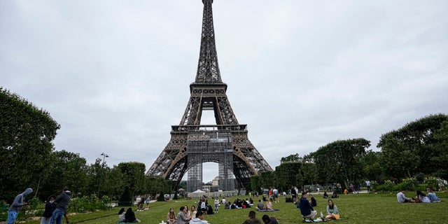 People relax at the Champ-de-Mars garden next to the Eiffel Tower in Paris, Friday, July 16, 2021. (AP)