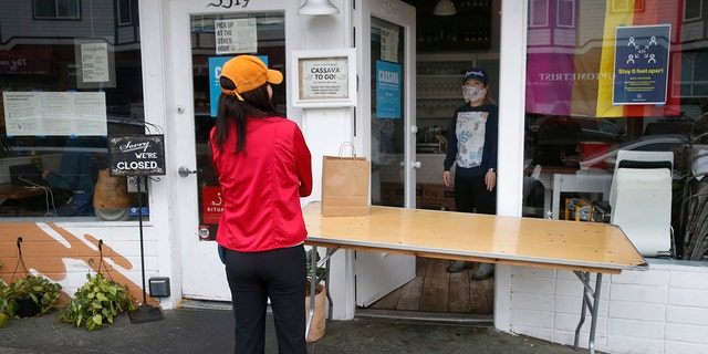 Cassava restaurant co-owner Yuka Ioroi, right, greets a customer picking up a to-go order in San Francisco, April 8, 2020. The restaurant plans to reopen indoor dining in August. (Getty Images)