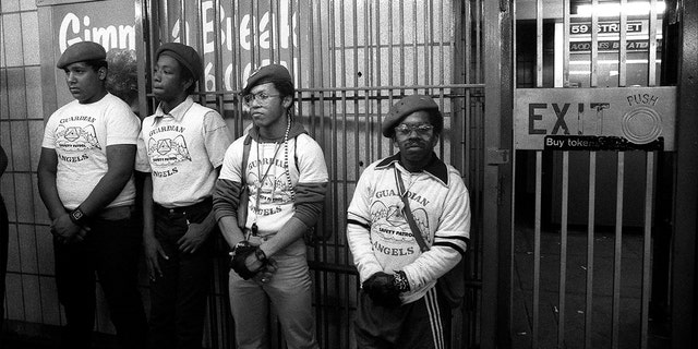 Portait of four members of the Guardian Angels' as they stand in a subway station, New York, New York, mid 1980s.