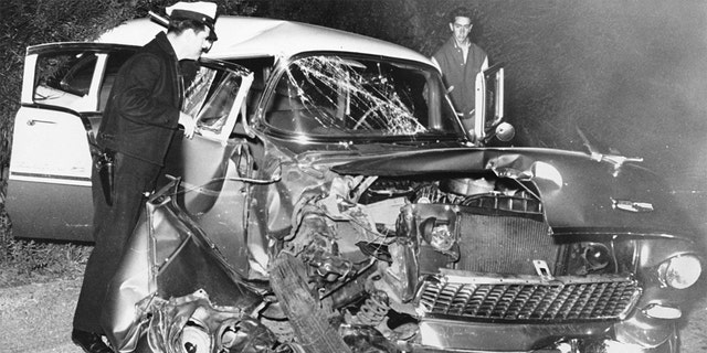 A policeman examines the wreckage of actor Montgomery Clift's car after it crashed into a power pole following a dinner party at the home of Michael Wilding and Elizabeth Taylor. Clift suffered serious head injuries.