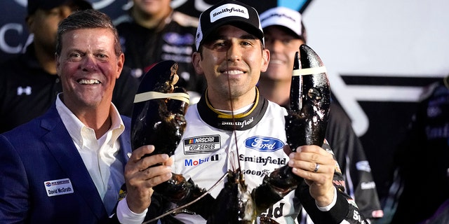 Aric Almirola smiles as he holds up a giant lobster after winning the NASCAR Cup Series auto race Sunday, July 18, 2021, in Loudon, N.H. At left is Dave McGrath, general manager of New Hampshire Motor Speedway. (AP Photo/Charles Krupa)