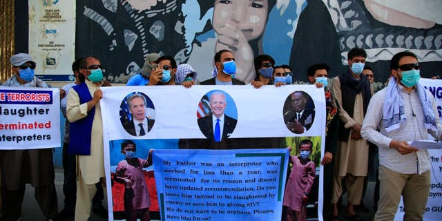 In this June 25, 2021 photo, Former Afghan interpreters hold placards during a demonstrations against the US government, in front of the US Embassy in Kabul, Afghanistan.