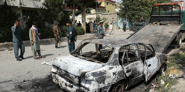 Security personnel inspect a damaged vehicle where rockets were fired from in Kabul, Afghanistan, Tuesday, July 20, 2021. (AP Photo/Rahmat Gul)
