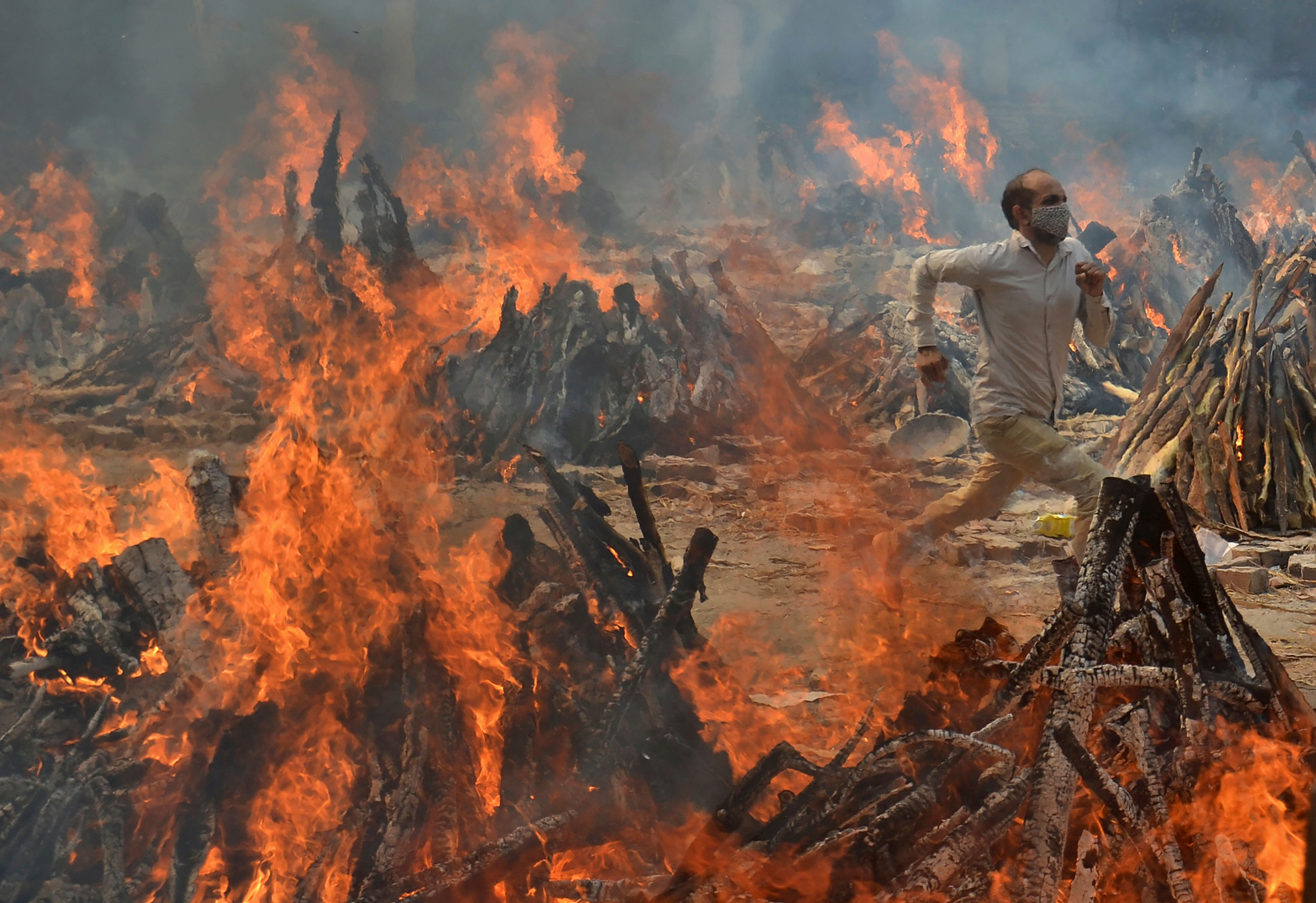 In this April 29, 2021, file photo, a man runs to escape heat emitting from the multiple funeral pyres of COVID-19 victims at