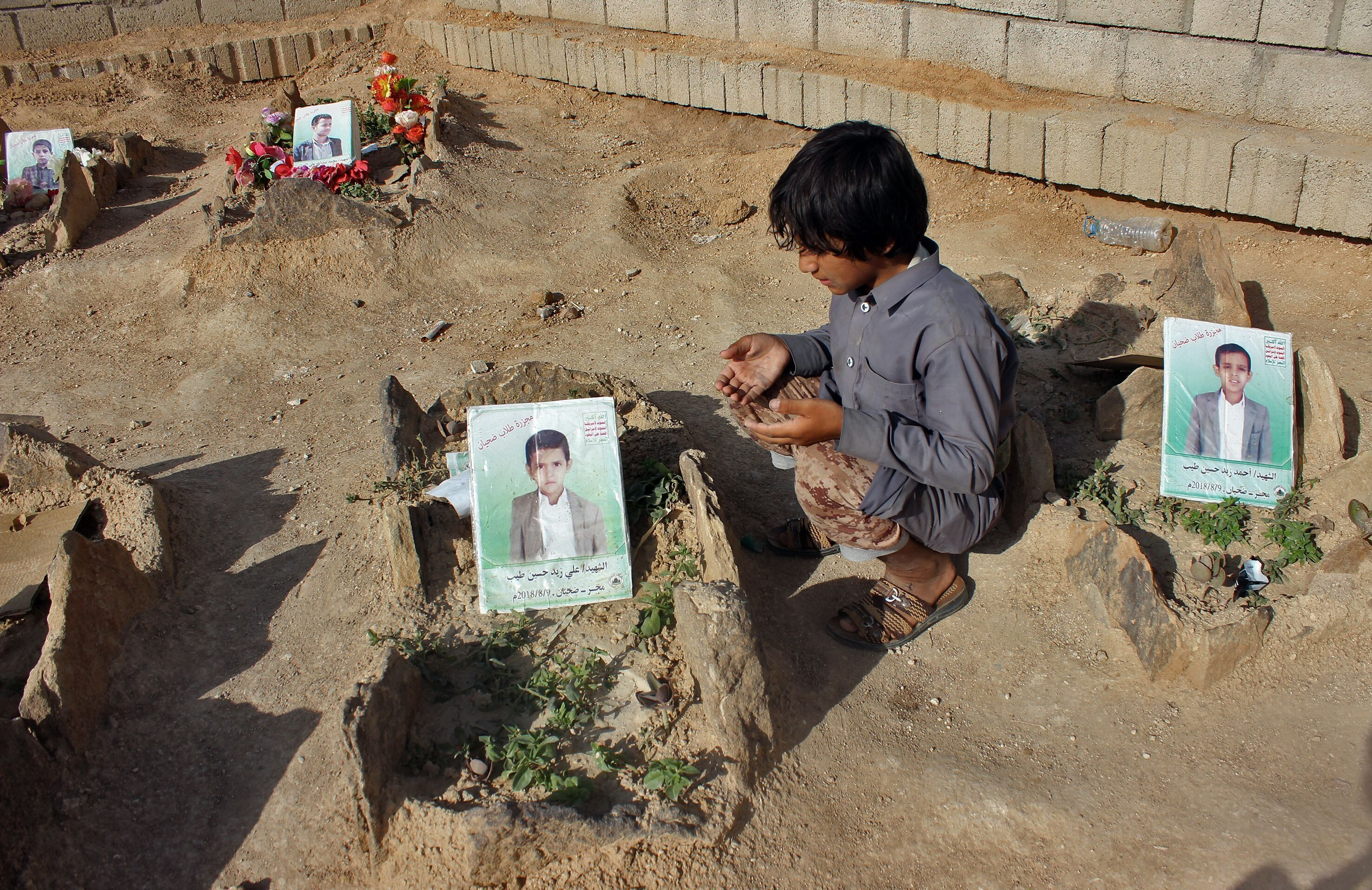 A Yemeni child at the graves of schoolboys who were killed in an August 2018 airstrike by a military coalition that included