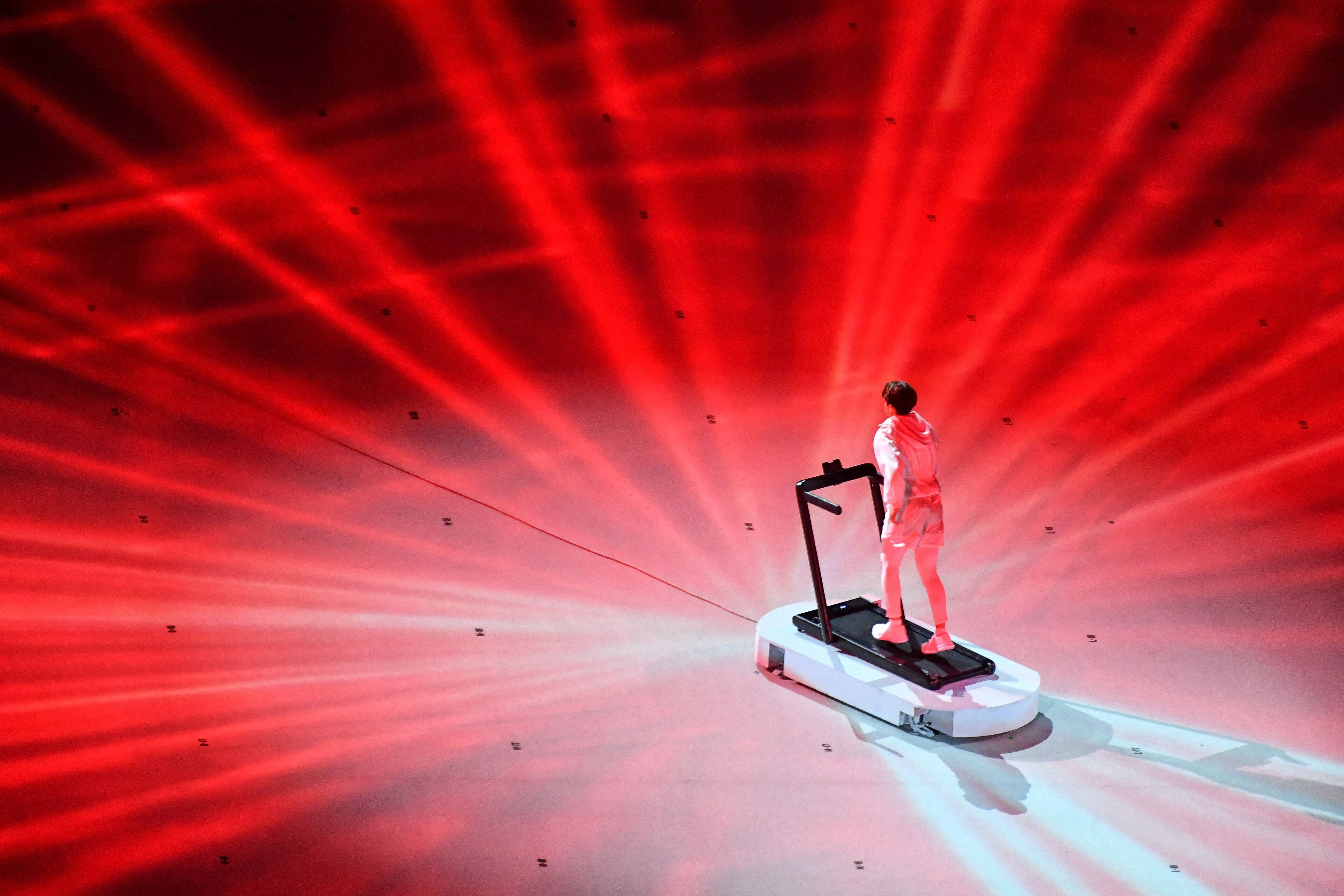 An overview shows a performer walking on a treadmill during the opening ceremony.