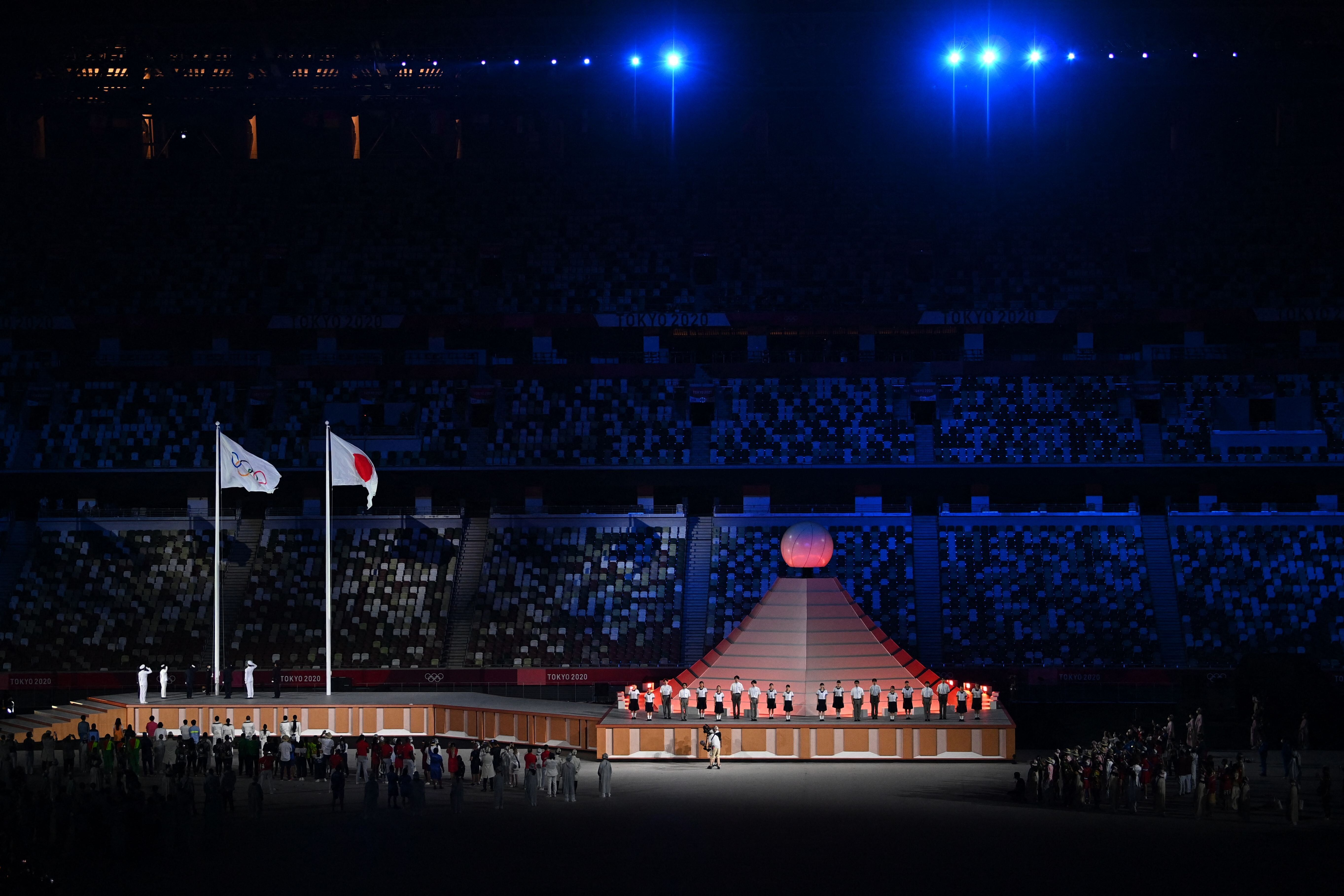The Olympic and Japanese flags sway in the wind.