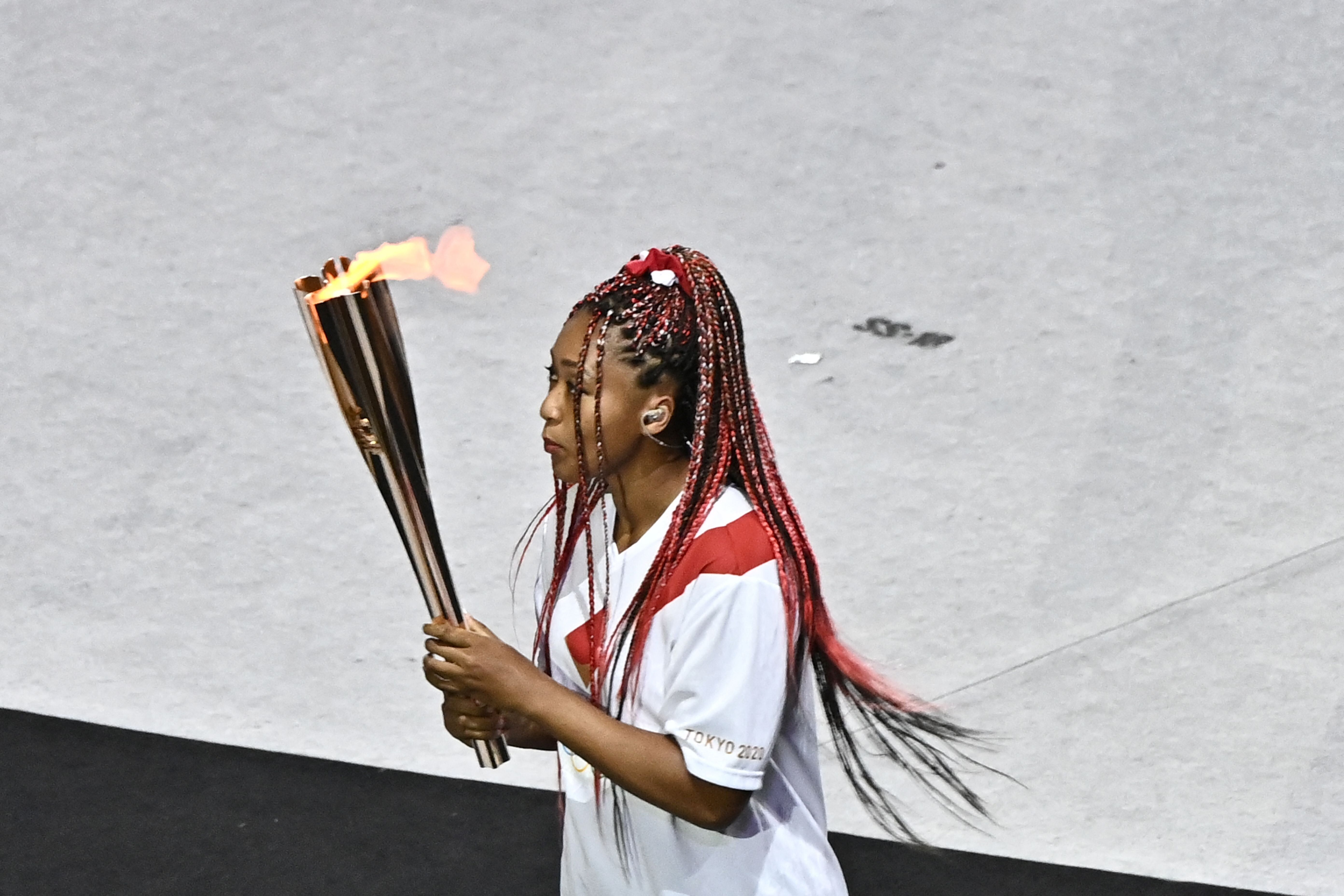 Team Japan's Naomi Osaka carries the Olympic torch.