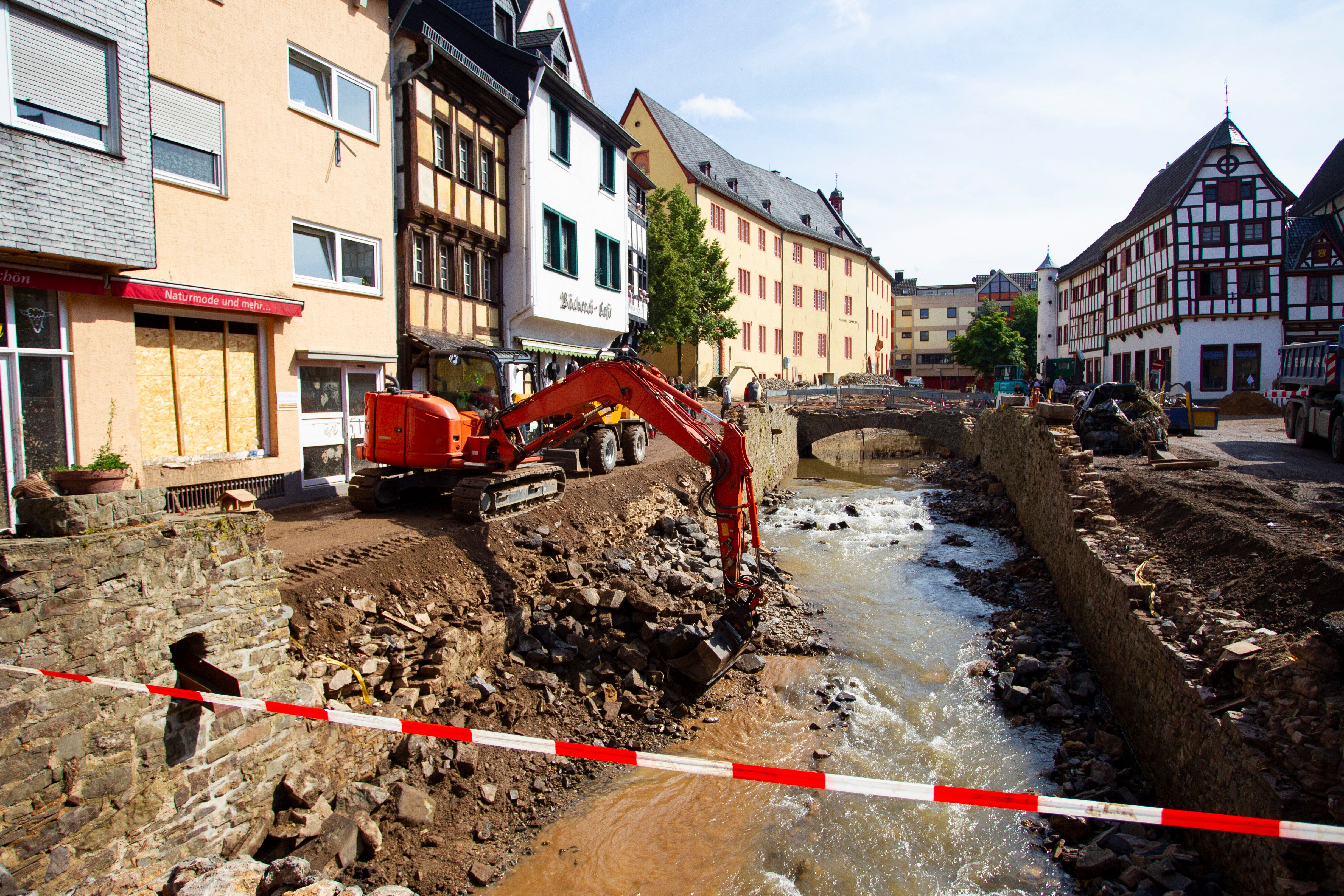 An excavator at work on the banks of the Erft River during clearing operations after flooding in North Rhine-Westphalia.