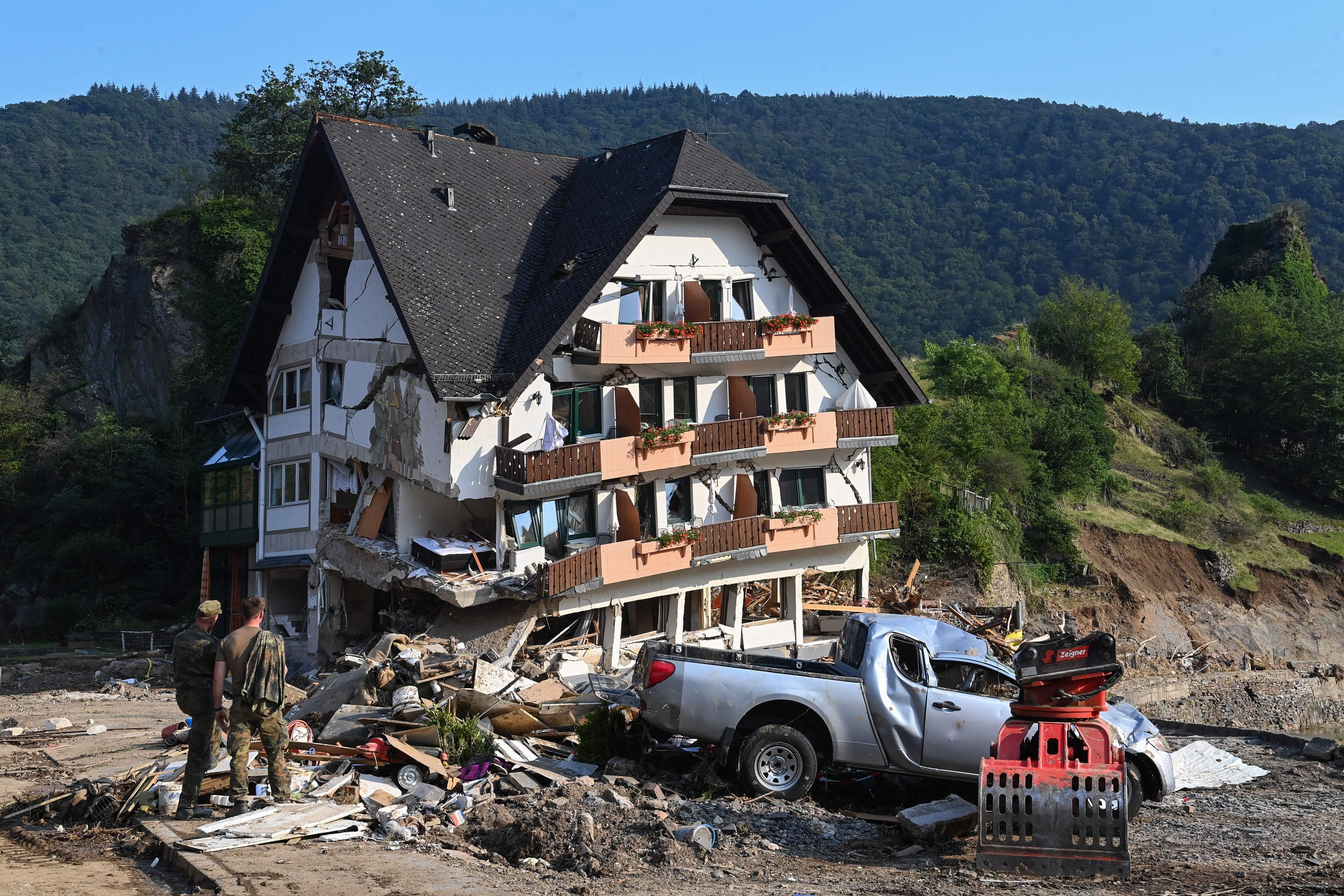 Military personnel stand beside a ruined country guest house in Laach, Germany.