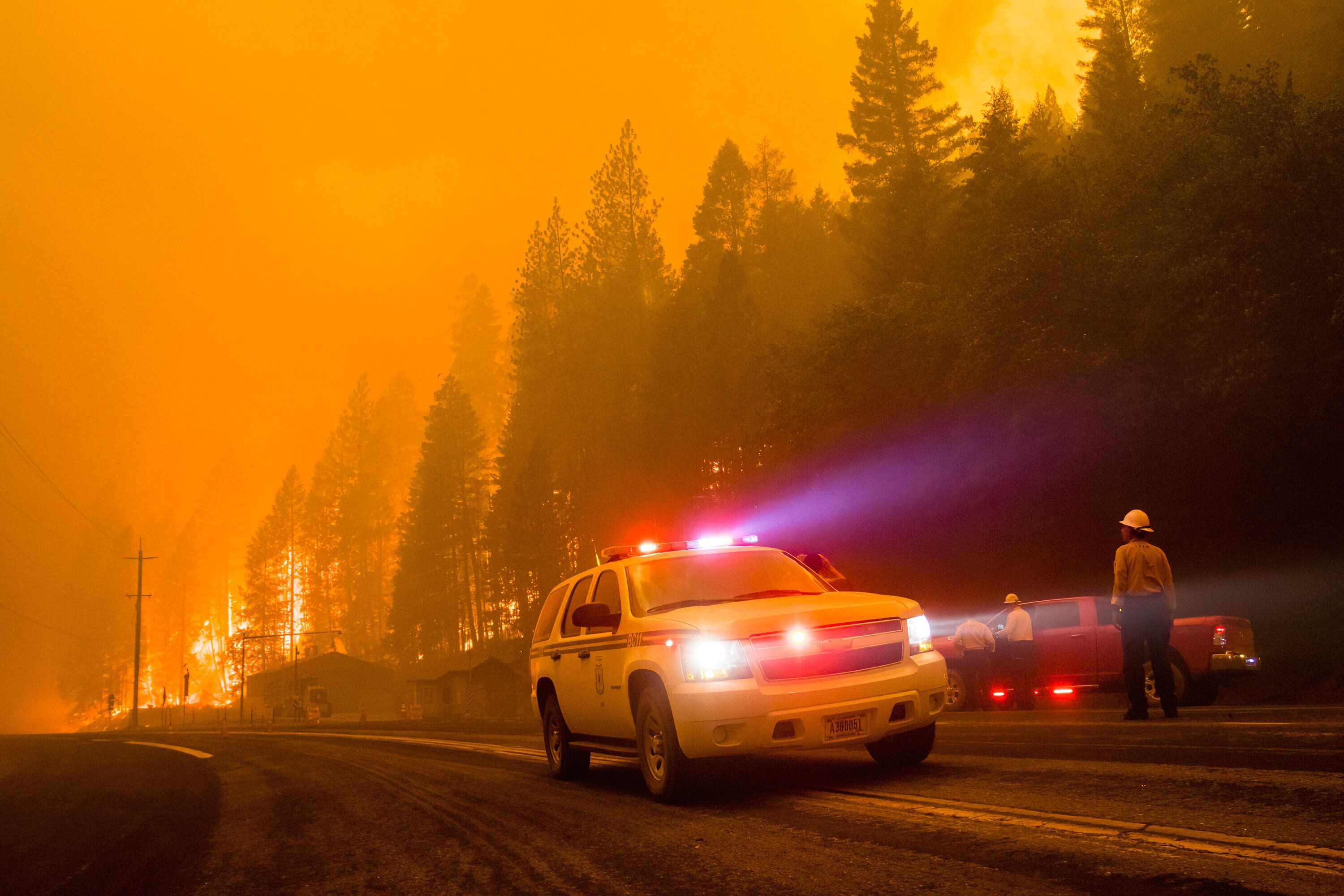 A firefighter vehicle turns around as active flames reach highway 70 in northern California.