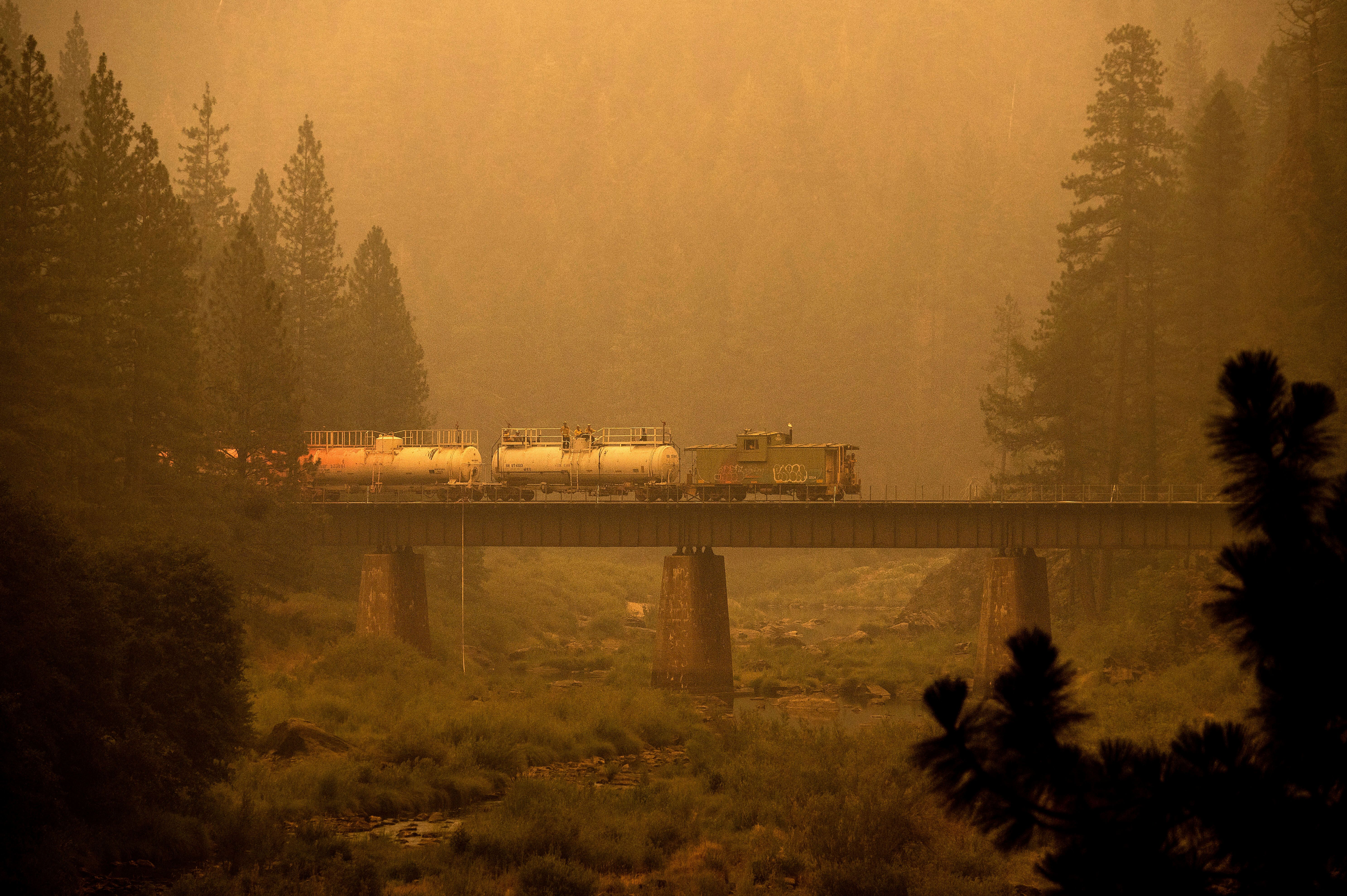 A fire train crosses a bridge as the Dixie Fire burns in Plumas County, Calif., on Saturday. The train is capable of spraying