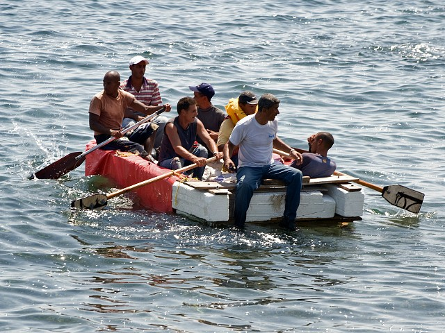 Seven would-be Cuban emigres remain in a homemade boat moments before being arrested by Cuban military agents after their attempt to escape from the island nation was thwarted by the sea currents, on June 4, 2009 in Havana. The boat-people's raft was brought back to the coast just in front of the US Interest Section office in Havana as they tried to cross the shark-infested Florida Straits. The United States, in another move aimed at thawing relations with Cuba, has offered to resume migration talks with the communist-ruled island almost six years after they were suspended. AFP PHOTO/ADALBERTO ROQUE (Photo credit should read ADALBERTO ROQUE/AFP/Getty Images)