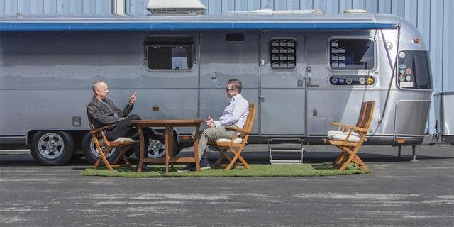 Tom Hanks talks to Bonhams Global Director of Motorsport Mark Osborne under the canopy of the 1992 Airstream travel trailer he's used on 18 filming sets.