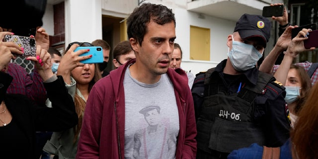 Roman Dobrokhotov, chief editor of The Insider walks surrounded police officers and journalists, in Moscow, Russia, Wednesday, July 28, 2021.