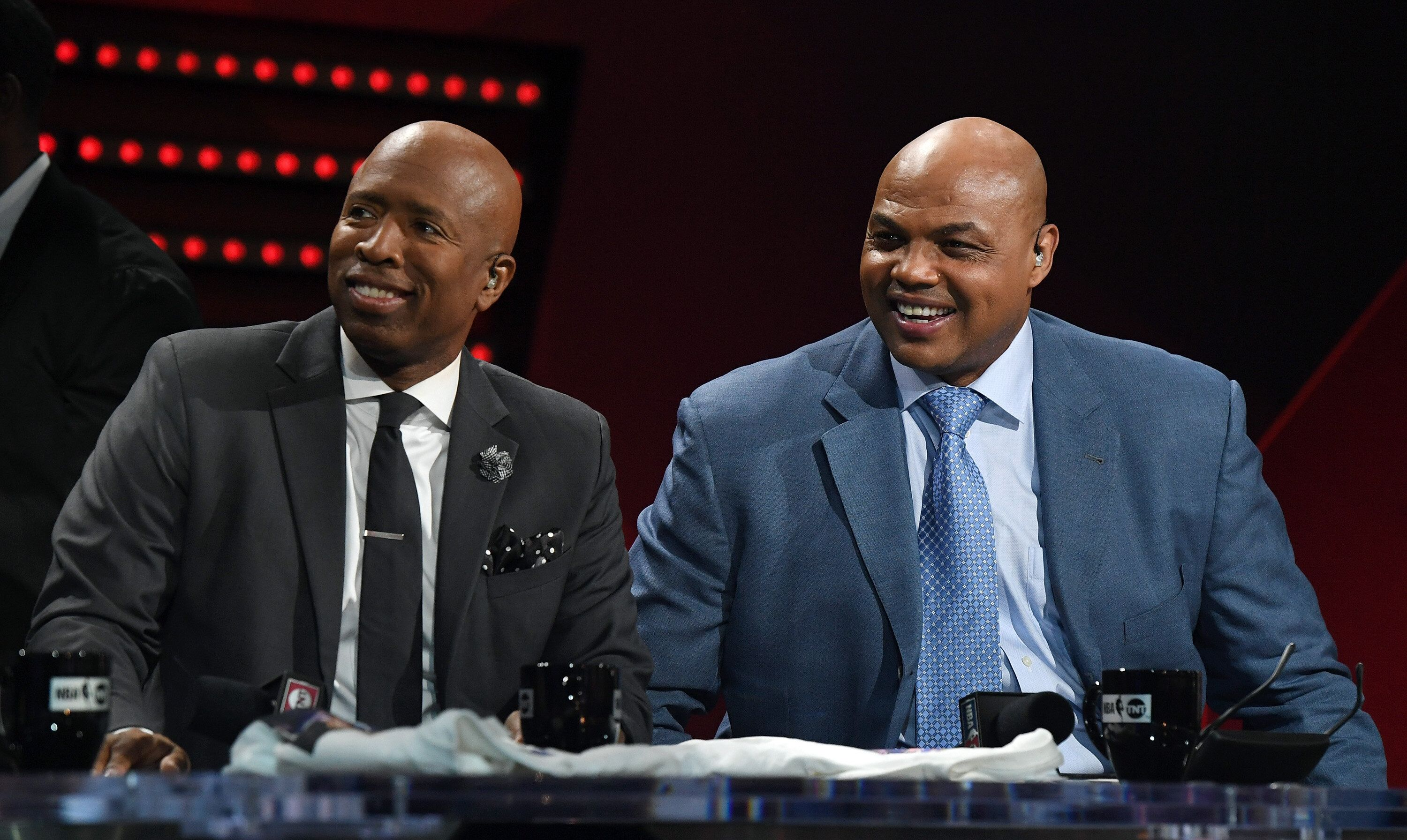 """NBA analysts Kenny Smith and Charles Barkley laugh during a live telecast of """"NBA on TNT"""" in 2017."""