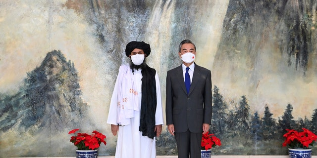 Taliban co-founder Mullah Abdul Ghani Baradar and Chinese Foreign Minister Wang Yi pose for a photo during their meeting in Tianjin, China, Wednesday, July 28, 2021. Wang met with a delegation of high-level Taliban officials as ties between them warm ahead of the U.S. pullout from Afghanistan.
