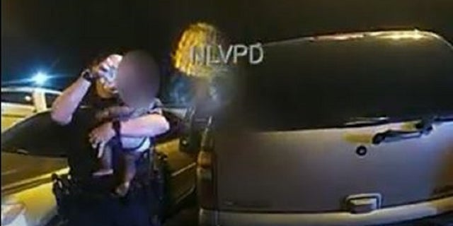 North Las Vegas police Sgt. Becky Salkoff pours water over a crying baby who was left in a hot car.