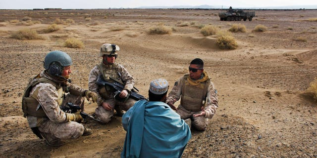 In this Friday, Dec. 11, 2009, file photo, United States Marine Sgt. Isaac Tate, left, and Cpl. Aleksander Aleksandrov, center, interview a local Afghan man with the help of a translator from the 2nd MEB, 4th Light Armored Reconnaissance Battalion on a patrol in the volatile Helmand province of southern Afghanistan. More than 200 Afghans were due to land Friday in the United States in the first of several planned evacuation flights for former translators and others as the U.S. ends its nearly 20-year war in Afghanistan. (AP Photo/Kevin Frayer, File)