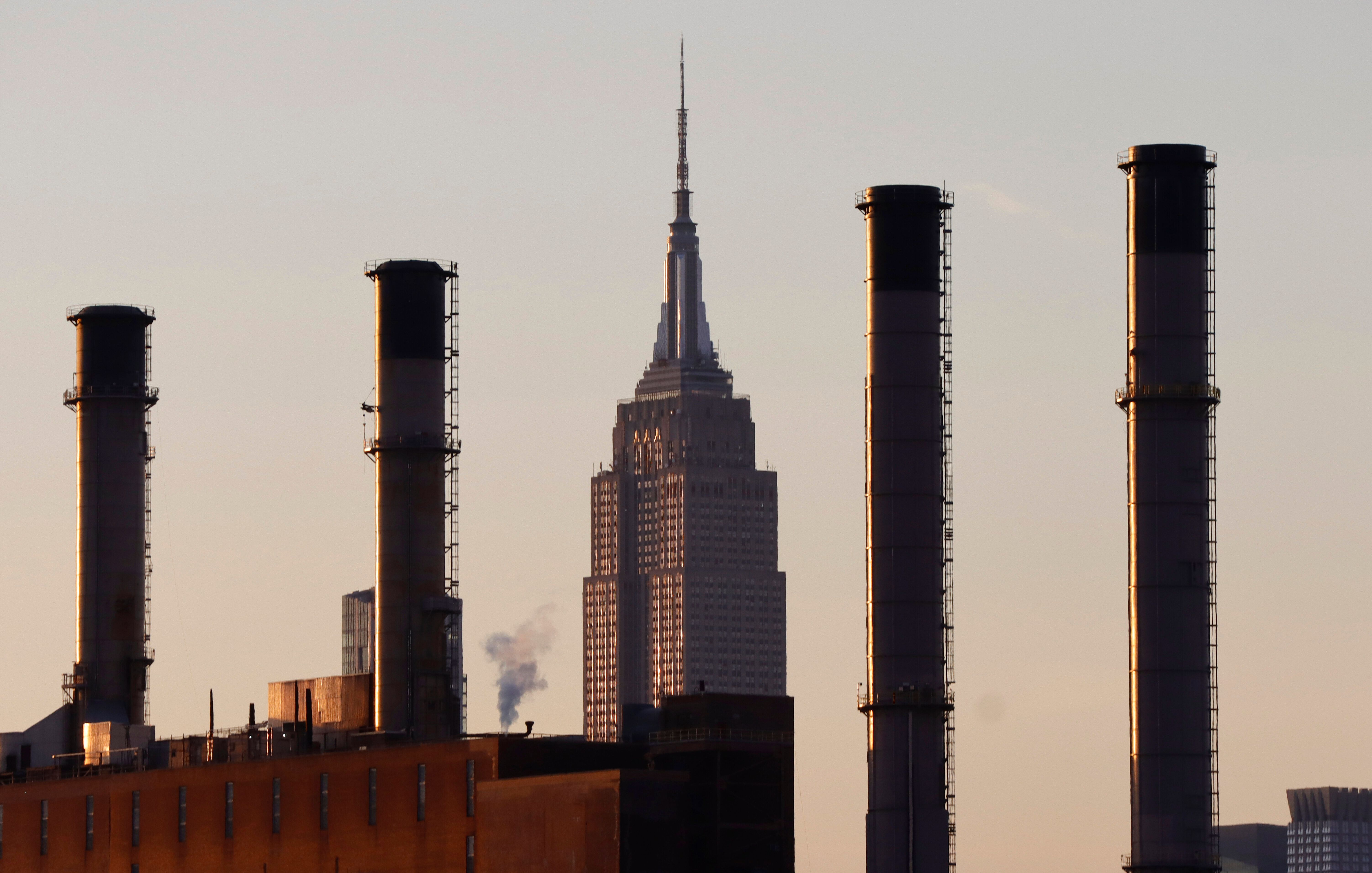 The sun sets on the Empire State Building as it sits behind smoke stacks of a ConEdison power plant.