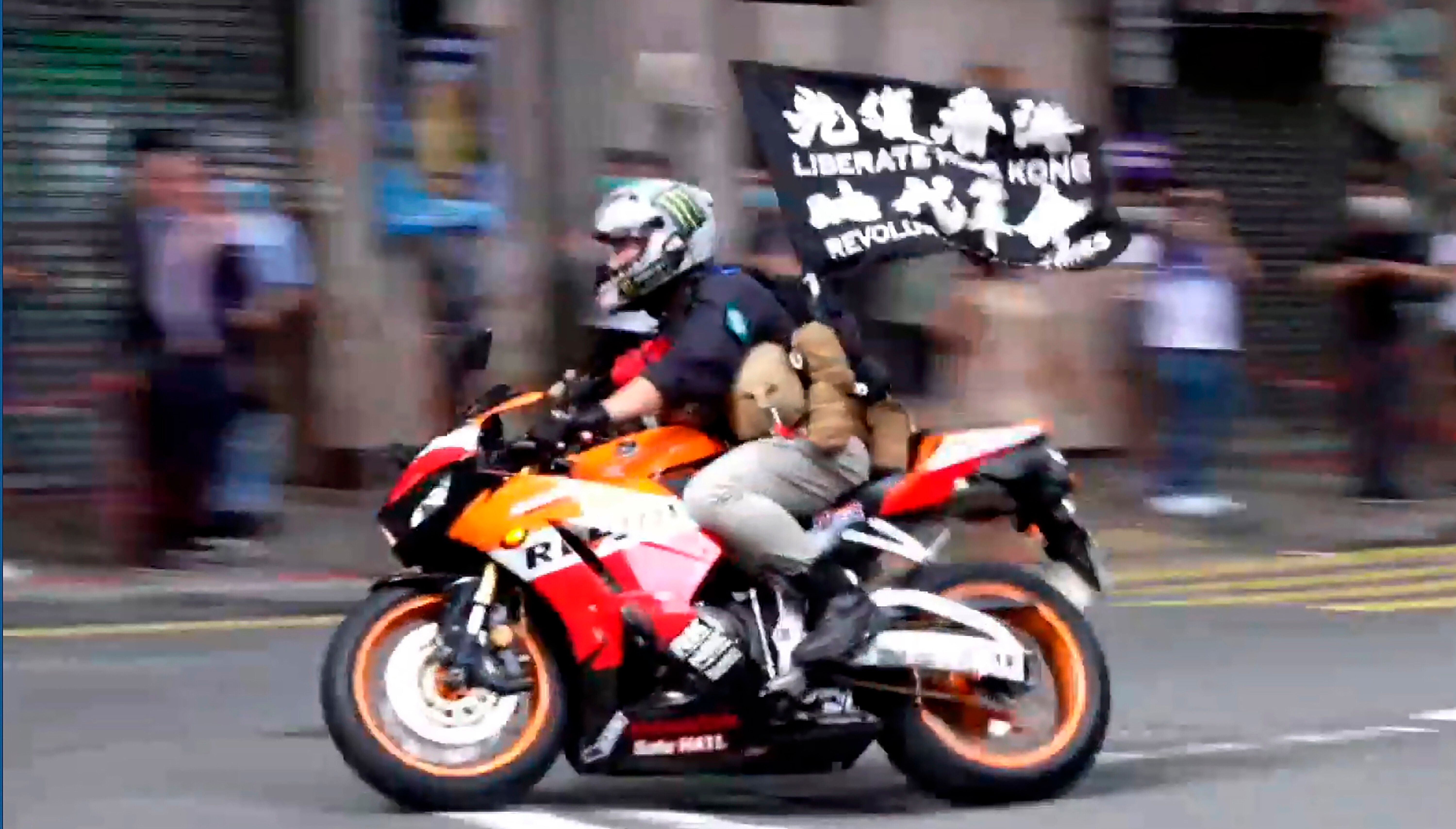 """In this July 1, 2020, file image made from video, motorcyclist Tong Ying-kit carries a flag reading """"Liberate Hong Kong, Revo"""