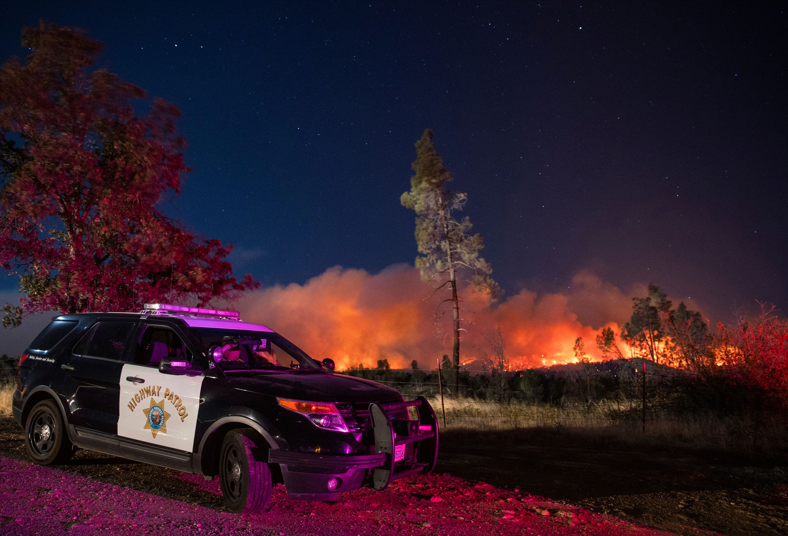 In this Sept. 28. 2020, file photo, a California Highway Patrol officer watches flames visible from the Zogg Fire near Igo, C